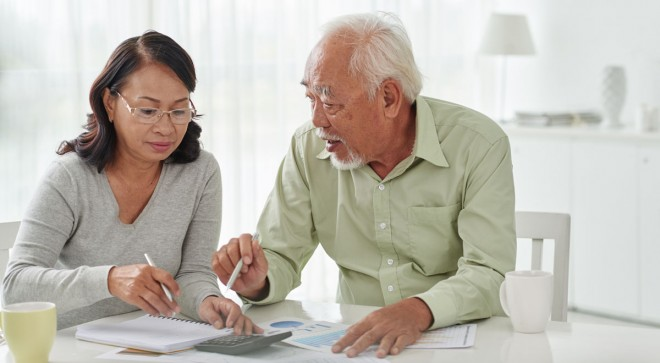 Senior Asian business couple discussing financial documents